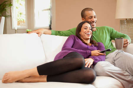 remote controls: Couple relaxing and watching television LANG_EVOIMAGES