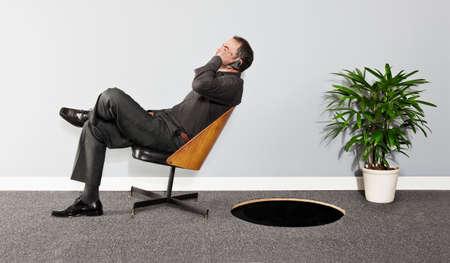 Business man tilting backwards on chair towards hole in floor LANG_EVOIMAGES
