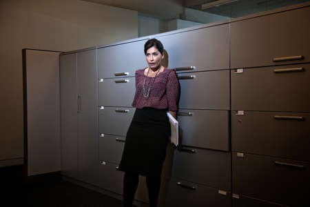 fedup: Office worker holding file behind back by filing cabinets
