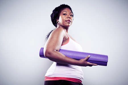 challenges ahead: Mid adult woman holding yoga mat