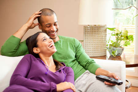 Happy couple relaxing and watching television