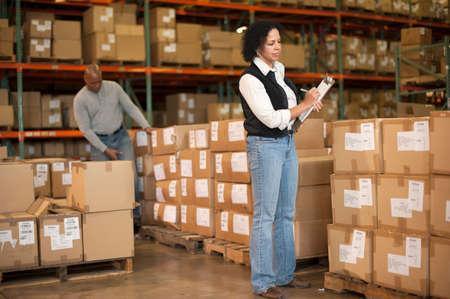 stocktaking: Female warehouse worker holding clipboard LANG_EVOIMAGES