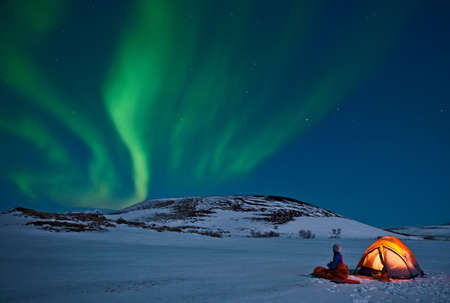 astonishing: Woman outside tent with Northern lights,Myvatn,Iceland