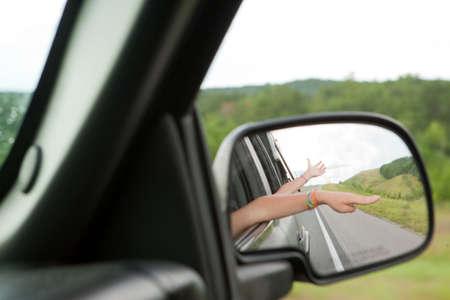 transportation: Hands reflected in car mirror