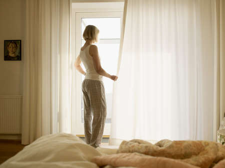 Mature woman wearing pyjamas opening bedroom curtains