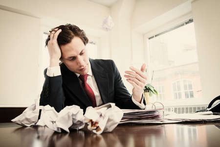 Young businessman with head in hands and crumpled paper