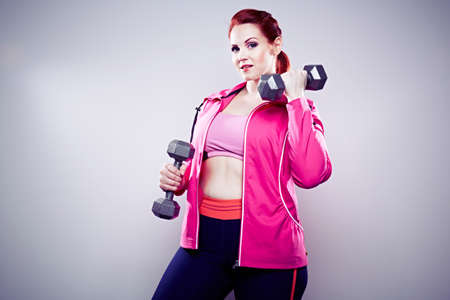 levantar peso: Young woman using hand weights LANG_EVOIMAGES