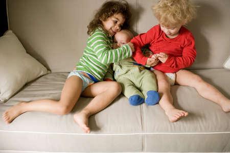Three siblings sitting on sofa