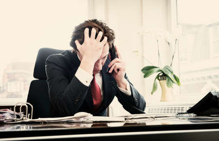 fed up: Young businessman on phone with head in hands