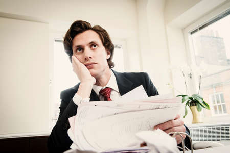 businessman pondering documents: Worried young businessman with paperwork LANG_EVOIMAGES