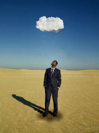 dry suit: Businessman standing under raincloud in desert