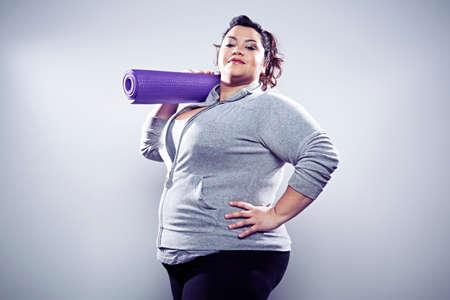 Mid adult woman carrying yoga mat on shoulder LANG_EVOIMAGES