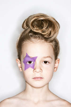 Blonde girl with purple star shape over eye LANG_EVOIMAGES
