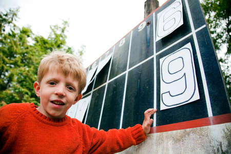 numeric: Young boy playing with numbers on scoreboard LANG_EVOIMAGES