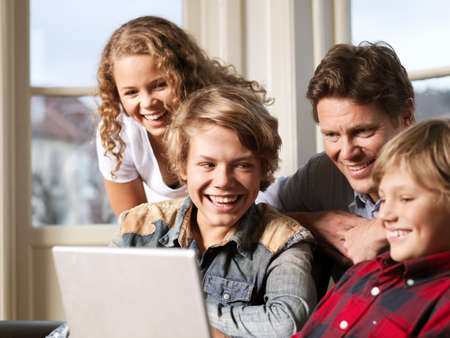 top 7: Father watching laptop with sons and daughter on sofa
