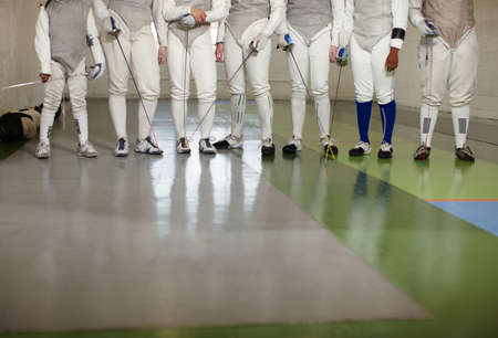 protective suit: Female fencers standing together in a row,low section