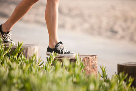 Young woman walking on wooden posts