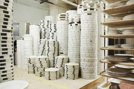 Stacks of white plates in pottery factory