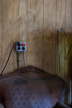 wood panelled: Electrical outlet and wires above old chair