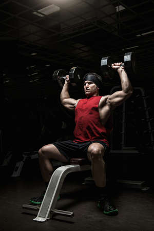 alice band: Muscular young man performing shoulder raises with dumbbells in gym LANG_EVOIMAGES