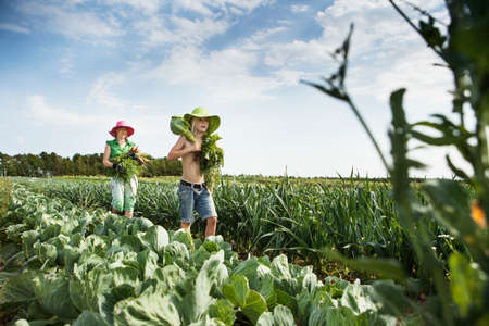 Mother and daughter carrying vegetables in field