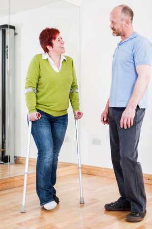 Woman using crutches talking to man