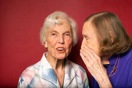 Portrait of two senior women whispering