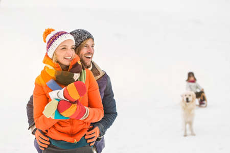 Couple in snow with girl and dog in background LANG_EVOIMAGES