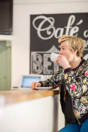 tea breaks: Woman drinking coffee at cafe counter