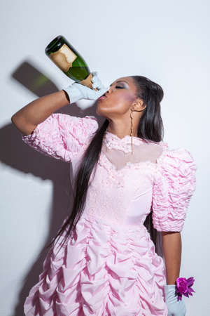 Young wearing prom dress and drinking champagne from bottle