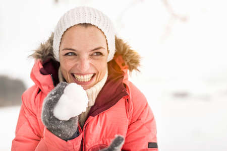 Woman holding snowball,laughing