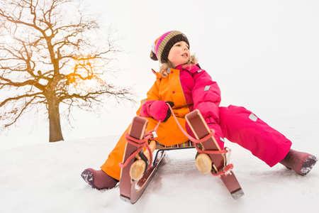 Girl on toboggan in snow