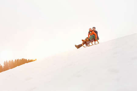 Couple on toboggan in snow LANG_EVOIMAGES