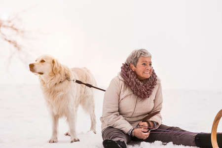 complicity: Woman sitting on snow with dog