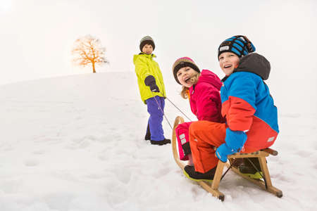 Boy pulling two friend through snow on toboggan LANG_EVOIMAGES