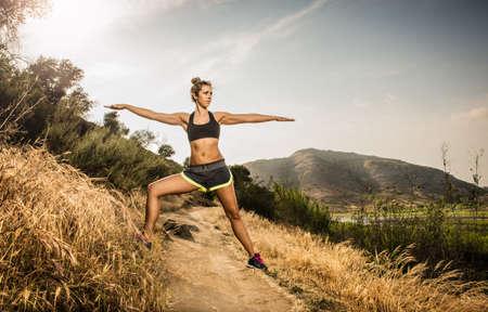 Female runner stretching in rural landscape