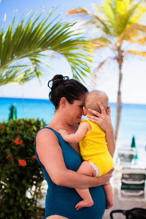 Mother in swimsuit holding baby daughter,St Maarten,Netherlands LANG_EVOIMAGES