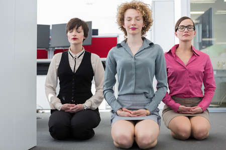 Three women meditating in office