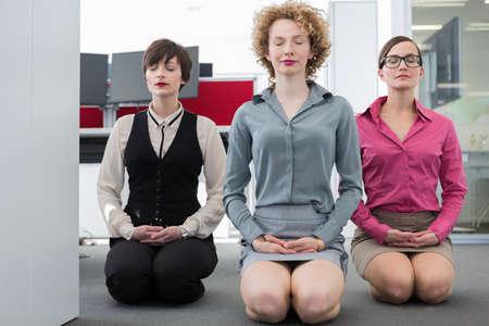 sinergia: Tres mujeres meditando en la oficina