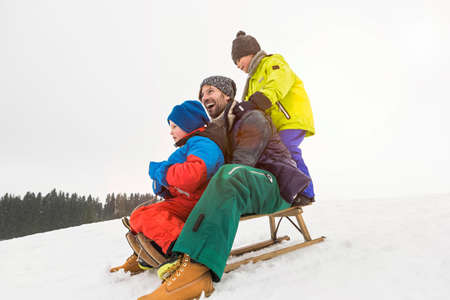 Man with two boys on toboggan in snow