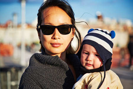 Mother wearing sunglasses holding baby boy