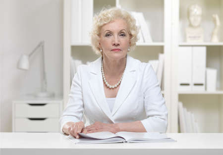 Serious senior businesswoman with book LANG_EVOIMAGES
