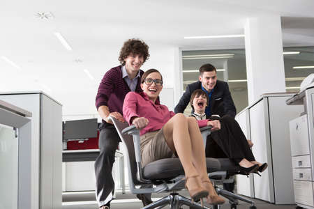 fed up: Office workers pushing women on office chairs