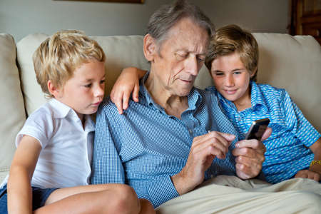 couch: Grandfather and grandsons looking at smartphone together