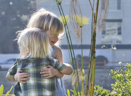 Toddlers hugging outdoors LANG_EVOIMAGES