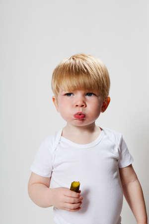 Boy eating gherkin LANG_EVOIMAGES