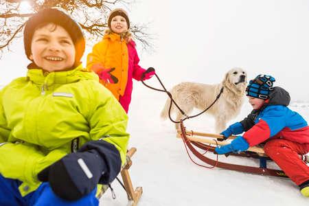 Three children on toboggans in snow