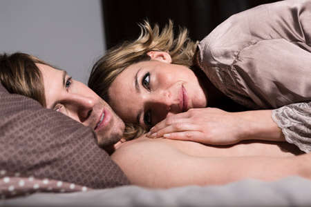Couple in bed,woman touching mans chest