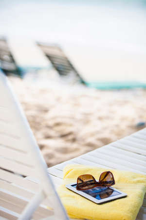 saint: Sunglasses,towel and electronic book on sun lounger LANG_EVOIMAGES