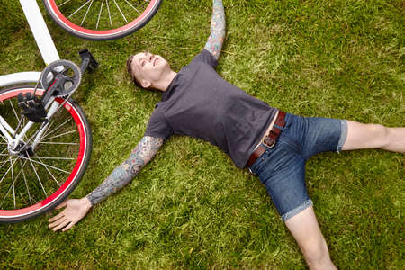Young tattooed man lying on grass